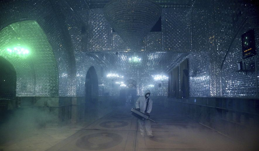 """A firefighter disinfects the shrine of Saint Saleh to help prevent the spread of the new coronavirus in northern Tehran, Iran, Friday, March, 6, 2020. A Health Ministry spokesman warned authorities could use unspecified """"force"""" to halt travel between major cities. (AP Photo/Ebrahim Noroozi)"""