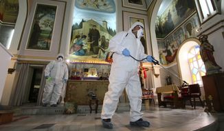Workers wearing protective clothing disinfect St Antonio Church, in Bayrakli district of Izmir, Turkey, Thursday, March 12, 2020, as a precaution against the coronavirus. Turkey's Health Minister Fahrettin Koca announced the first case of COVID-19 coronavirus in Turkey on Wednesday. For most people, the new coronavirus causes only mild or moderate symptoms. For some it can cause more severe illness.(AP Photo/Emre Tazegul)