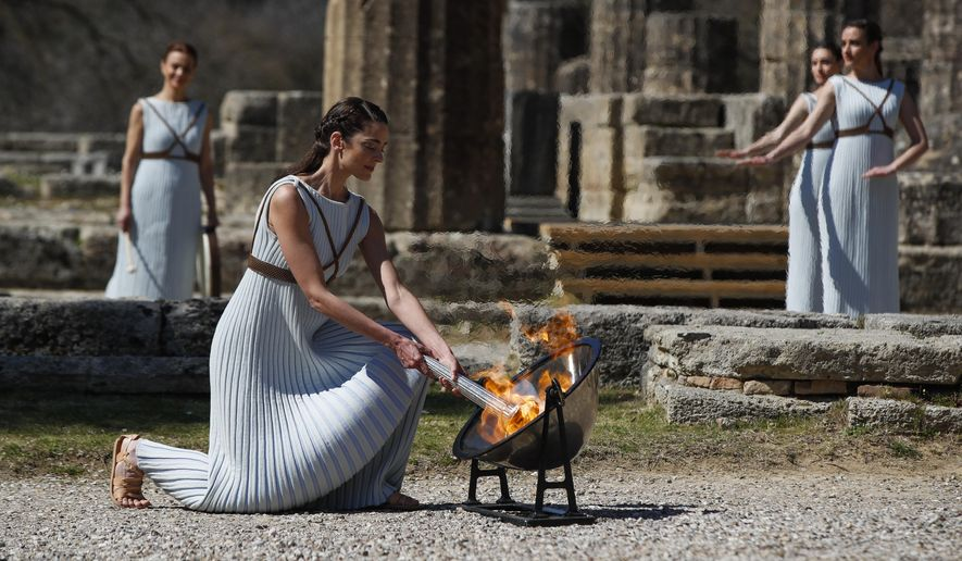 Greek actress Xanthi Georgiou, playing the role of the High Priestess, lights up the torch during the flame-lighting ceremony at the closed Ancient Olympia site, birthplace of the ancient Olympics in southern Greece, Thursday, March 12, 2020. Greek Olympic officials are holding a pared-down flame-lighting ceremony for the Tokyo Games due to concerns over the spread of the coronavirus. Both Wednesday's dress rehearsal and Thursday's lighting ceremony are closed to the public, while organizers have slashed the number of officials from the International Olympic Committee and the Tokyo Organizing Committee, as well as journalists at the flame-lighting. (AP Photo/Thanassis Stavrakis)
