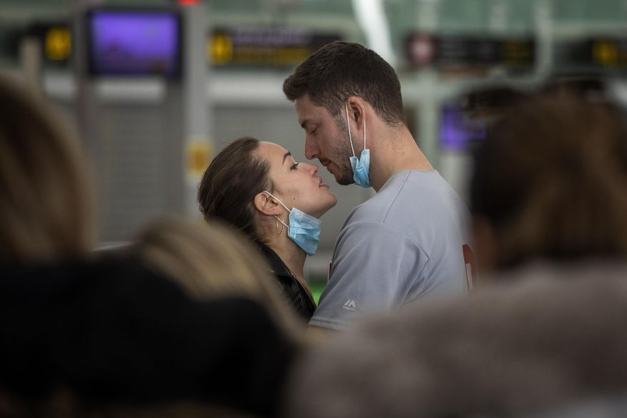 A couple kiss,  at the Barcelona airport, Spain, Thursday, March 12, 2020. President Donald Trump, who had downplayed the coronavirus for weeks, suddenly struck a different tone, announcing strict rules on restricting travel from much of Europe to begin this weekend. For most people, the new coronavirus causes only mild or moderate symptoms, such as fever and cough. For some, especially older adults and people with existing health problems, it can cause more severe illness, including pneumonia. (AP Photo/Emilio Morenatti)