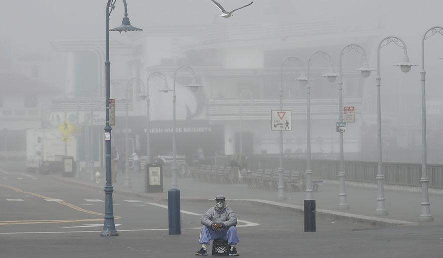 A street performer sits alone at Fisherman's Wharf in San Francisco, Thursday, March 12, 2020.  California Gov. Gavin Newsom said Thursday that sweeping guidance for Californians to avoid unnecessary gatherings to avoid the spread of the new coronavirus will likely extend beyond March. The statewide guidance applies to sporting events, concerts and even smaller social gatherings in places where people can't remain at least 6 feet (2 meters) apart. For most people, the new coronavirus causes only mild or moderate symptoms. For some it can cause more severe illness. (AP Photo/Jeff Chiu)