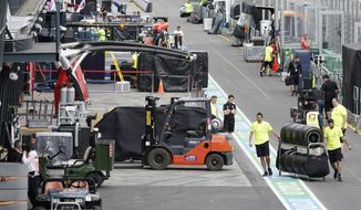 Workers pack up in pit lane after the cancellation of the Australian Formula One Grand Prix in Melbourne, Friday, March 13, 2020. The first F1 Grand Prix of the season was canceled two hours before the first official practice was set to start Friday after organizers relented to pressure to call it off amid the spreading coronavirus. (Michael Dodge/AAP Image via AP)