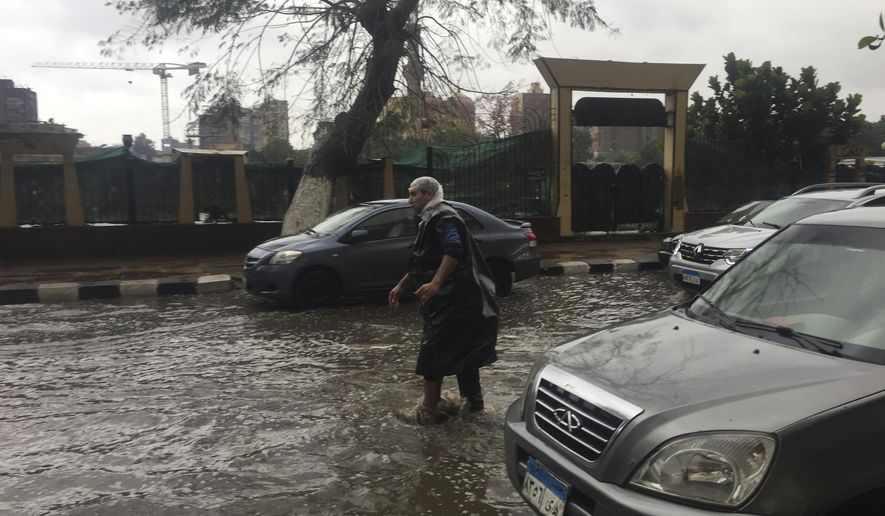 A man wears makeshift rain gear as he navigates a flooded road after heavy rains in the Zamalek district of Cairo, Egypt, Thursday, March 12, 2020. Thunderstorms packing heavy rains and lightning caused widespread flooding in Egypt on Thursday, killing several people and causing authorities to shut down schools and an airport, officials said. (AP Photo/Maya Alleruzzo)