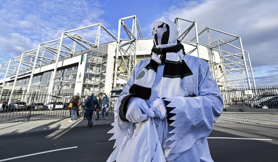 A Borussia fan dressed as ghost stands in front of the stadium prior the German Bundesliga soccer match between Borussia Moenchengladbach and 1.FC Cologne in Moenchengladbach, Germany, Wednesday, March 11, 2020. It is the first Bundesliga match played behind closed doors without spectators due to the coronavirus outbreak. For most people, the new coronavirus causes only mild or moderate symptoms, such as fever and cough. For some, especially older adults and people with existing health problems, it can cause more severe illness, including pneumonia. (AP Photo/Martin Meissner)