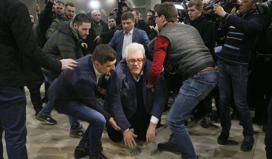 Advisor to Secretary of Ukraine's National Security and Defense Council on reintegration and restoration of the occupied territories of the Donetsk region Serhiy Syvokho is helped to stand from the floor in Kyiv, Ukraine, Thursday, March 12, 2020.  Syvokho was pushed to the floor by veterans of the military conflict in the country's east, during presentation of his national program of reconciliation and unity with the separatist region. Syvokho was a showman, creative producer of Studio Kvartal 95 entertainment program led at that time by current President Volodymyr Zelenskiy. (AP Photo/Efrem Lukatsky)