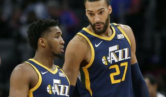 In this Saturday, March 7, 2020, file photo, Utah Jazz center Rudy Gobert (27) talks with guard Donovan Mitchell, left, during the second half of an NBA basketball game against the Detroit Pistons, in Detroit. Both players have tested positive for the coronavirus.  Gobert's test result forced the NBA to suspend the season. (AP Photo/Duane Burleson, File)