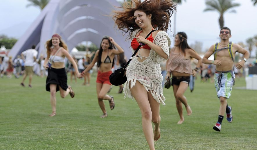 This April 13, 2012 file photo shows festivalgoers running toward the main stage at the 2012 Coachella Valley Music and Arts Festival in Indio, Calif. (AP Photo/Chris Pizzello, File)