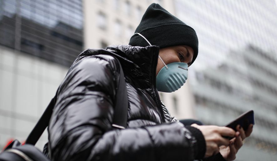 A pedestrian uses her phone while wearing a face mask in New York City's Herald Square on Thursday, March 12, 2020. (AP Photo/John Minchillo) **FILE**