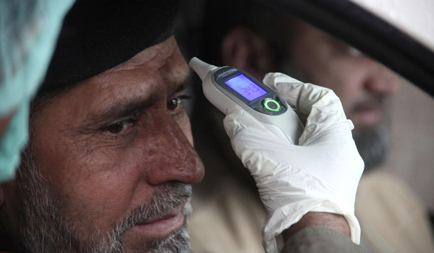 A health official checks the body temperature of a government employee in Peshawar, Pakistan, Thursday, March 12, 2020. For most people, the new coronavirus causes only mild or moderate symptoms, such as fever and cough. For some, especially older adults and people with existing health problems, it can cause more severe illness, including pneumonia. (AP Photo/Muhammad Sajjad)