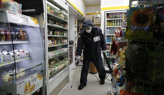 Members of the national reserve units wear protective gear as they disinfect against the new coronavirus at a convenient store in Seoul, South Korea, Thursday, March 12, 2020. For most people, the new coronavirus causes only mild or moderate symptoms, such as fever and cough. For some, especially older adults and people with existing health problems, it can cause more severe illness, including pneumonia. (AP Photo/Lee Jin-man)