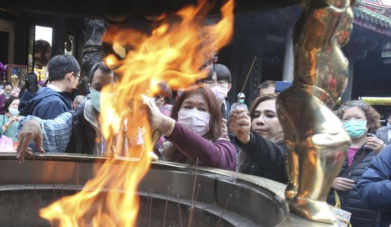 People wear face masks to protect against the spread of the coronavirus as they pray at the popular Longshan Temple in Taipei, Taiwan, Thursday, March 12, 2020. For most people, the new coronavirus causes only mild or moderate symptoms. For some it can cause more severe illness. (AP Photo/Chiang Ying-ying)