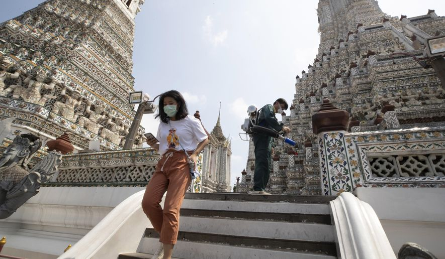 A tourist wearing a protective mask as a worker sprays disinfectant at Temple of Dawn in Bangkok, Thailand, Thursday, March 12, 2020. For most people, the new coronavirus causes only mild or moderate symptoms. For some it can cause more severe illness. (AP Photo/Sakchai Lalit)