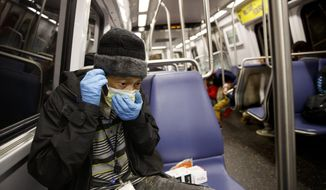 Andre of Washington, D.C., rides the Metro subway Green Line train in Washington, Friday, March, 13, 2020. He wears two face masks and gloves to protect his children and grandchildren from the coronavirus. He doesn't want to bring it home. (AP Photo/Carolyn Kaster)
