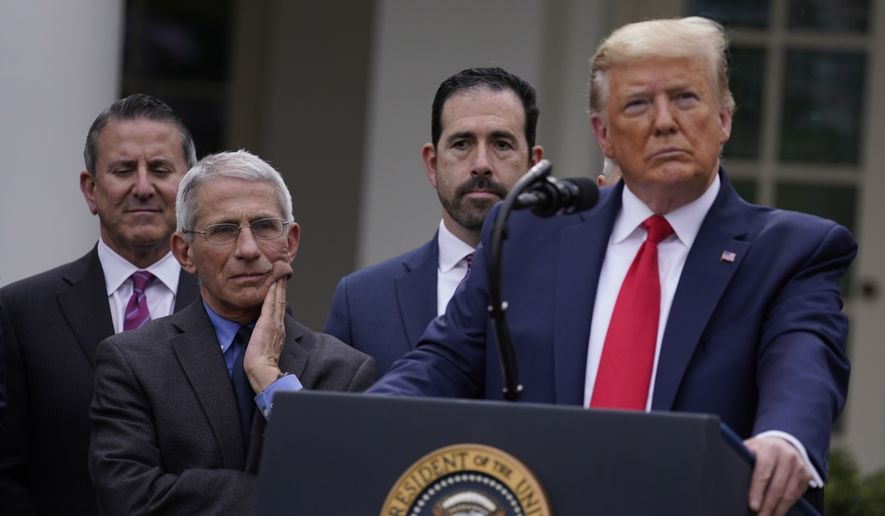 Dr. Anthony Fauci, director of the National Institute of Allergy and Infectious Diseases, second from left, and President Donald Trump, right, listen during a news conference about the coronavirus in the Rose Garden of the White House, Friday, March 13, 2020, in Washington. (AP Photo/Evan Vucci)