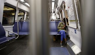 A commuter has her clothing pulled up to cover her mouth and nose as she rides the Green Line of the Metro subway train in Washington, Friday, March, 13, 2020. Commuter numbers are down because of the coronavirus outbreak. (AP Photo/Carolyn Kaster)