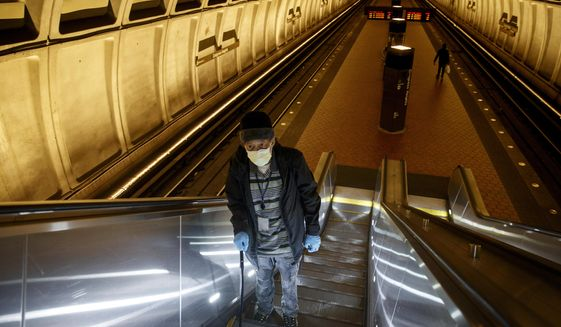 Andre of Washington, D.C., rides the escalator up at the Metro subway Congress Heights train station in Washington, Friday, March, 13, 2020. He wears two face masks and gloves to protect his children and grandchildren from the coronavirus. He doesn't want to bring it home. (AP Photo/Carolyn Kaster)