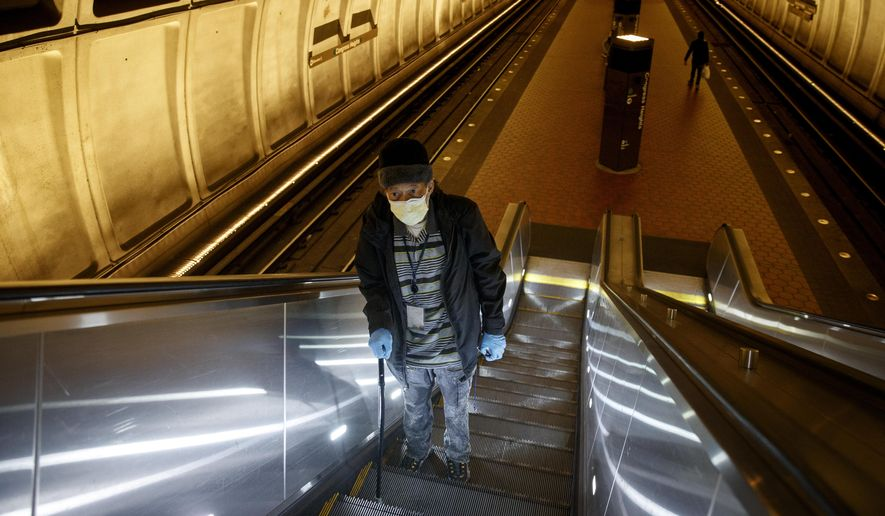 In this file photo, a Washington, D.C., man rides the escalator up at the Metro subway Congress Heights train station in Washington, Friday, March 13, 2020.  (AP Photo/Carolyn Kaster) ** FILE **