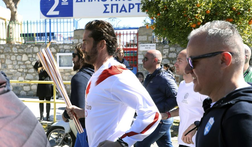 "US actor Gerard Butler runs as a torchbearer during the Olympic torch relay of the 2020 Tokyo Olympic Games in the southern Greek town of Sparta, Friday, March 13, 2020. Greece's Olympic committee says it is suspending the rest of its torch relay for the Olympic flame due to the ""unexpectedly large crowd"" that gathered to watch despite repeated requests for the public to stay away to prevent the spread of the new coronavirus. (AP Photo) ** FILE **"