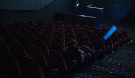 A sole spectator watches a film in a movie theatre in Budapest, Hungary, Thursday, March 12, 2020. Effective from today, cinemas in Hungary are restricted to sell a maximum of 99 tickets for a show as the Hungarian government declared a state of emergency in response to the novel coronavirus, and prohibited all indoor events with more than 100 participants and outdoor events attended by more than 500 participants. (Marton Monus/MTI via AP)