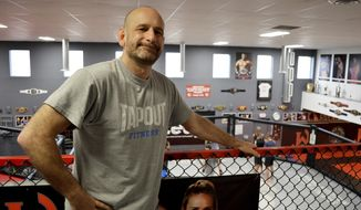 "FILE - In this Dec. 11, 2019, file photo, Greg Jackson, co-owner of Jackson Wink MMA Academy, stands above his training facility in Albuquerque, N.M. Jackson Wink MMA Academy, the storied mixed martial arts gym that has trained UFC light heavyweight champion Jon ""Bones"" Jones, said Friday, March 13, 2020, it's adjusting its training amid rising cases of the new coronavirus. (AP Photo/Russell Contreras, File)"