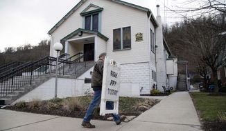 "In this Feb. 28, 2020 file photo, Mayor David Depretis of Baldwin Borough brings in the sign announcing ""Fish Fry Today,"" after Holy Angels parish sold out of fish in Pittsburgh, Pa. The parish church prepares 2,000 pounds of fish and often sells out early, according to organizer Cindy Depretis, who is married to the mayor. On March 12, Pittsburgh Bishop David Zubik suggested that people enjoy the fish fries with a take-out order rather than dining in due to virus concerns. (AP Photo/Rebecca Droke)"