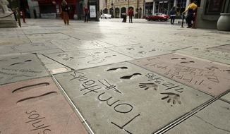 The cement inscription of actor Tom Hanks sits in the nearly empty forecourt of the TCL Chinese Theatre, Thursday, March 12, 2020, in the Hollywood section of Los Angeles. Hanks and his wife, actress-singer Rita Wilson, have tested positive for the coronavirus, the actor said in a statement Wednesday. For most people, the new coronavirus causes only mild or moderate symptoms. For some it can cause more severe illness. (AP Photo/Chris Pizzello)