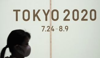 A woman walks past a large display promoting the Tokyo 2020 Olympics in Tokyo, Friday, March 13, 2020. U.S. President Donald Trump's suggestion to postpone the Tokyo Olympics for a year because of the spreading coronavirus was immediately shot down by Japan's Olympic minister. For most people, the new coronavirus causes only mild or moderate symptoms. For some it can cause more severe illness. (AP Photo/Jae C. Hong)