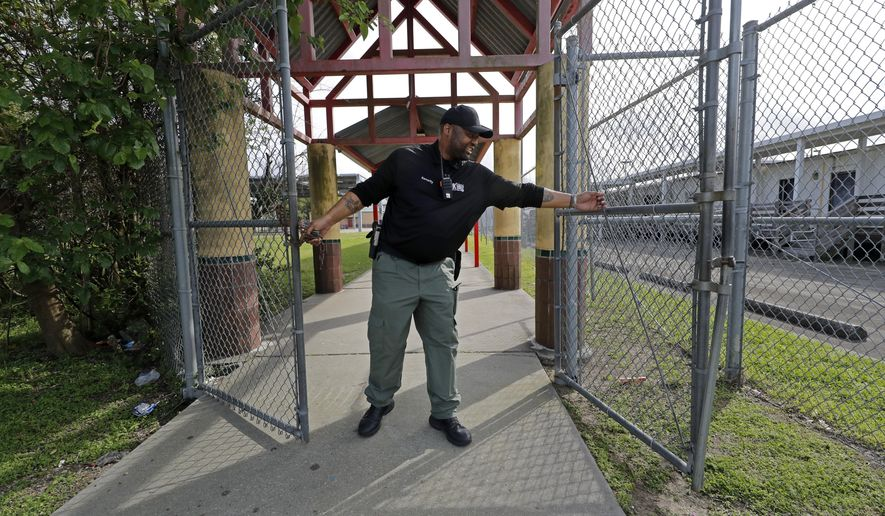 School Resource Officer Donald Lee locks the gates of the Dr. Martin Luther King, Jr. Elementary School for Science and Technology, after all the students left, in New Orleans, Friday, March 13, 2020. Louisiana Gov. John Bel Edwards on Friday closed K-12 public schools across the state for roughly a month and banned gatherings of more than 250 people in an effort to slow the spread of the coronavirus. For most people, the new coronavirus causes only mild or moderate symptoms. For some it can cause more severe illness. (AP Photo/Gerald Herbert)