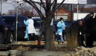Medical staff wearing safety garments assist drivers at a new coronavirus drive-up test clinic, one of several in the metropolitan Twin Cities area, Friday, March 13, 2020, in Bloomington, Minn. The vast majority of people recover from the new coronavirus. According to the World Health Organization, most people recover in about two to six weeks, depending on the severity of the illness. (AP Photo/Jim Mone)