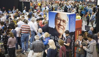 FILE- In this May 5, 2017 file photo, an image of Warren Buffett towers over Berkshire Hathaway shareholders in Omaha, Neb, at the Berkshire Hathaway shareholders meeting. Warren Buffett told shareholders on Friday May 13, 2020, that they won't be allowed to physically attend the company's May 2 annual meeting in Omaha because of the coronavirus threat.  For most people, the new coronavirus causes only mild or moderate symptoms, such as fever and cough. For some, especially older adults and people with existing health problems, it can cause more severe illness, including pneumonia. The vast majority of people recover . (AP Photo/Nati Harnik)