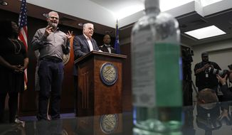 With a bottle of hand sanitizer on a table nearby, Nevada Gov. Steve Sisolak announces a state of emergency amid coronavirus fears, at a news conference Thursday, March 12, 2020, in Las Vegas. (AP Photo/John Locher)