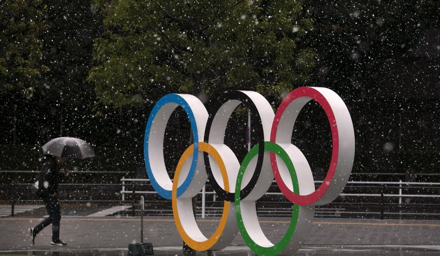 Snow falls on the Olympic rings near the New National Stadium in Tokyo, Saturday, March 14, 2020. (AP Photo/Jae C. Hong)