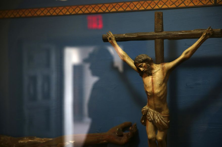 A man is reflected in a glass case containing a statue of a crucified Jesus Christ at the museum of the Mission San Xavier del Bac in Tucson, Ariz., Friday, Feb. 21, 2020. San Xavier was founded as a Catholic mission by Father Eusebio Kino in 1692 when Southern Arizona was part of New Spain. (AP Photo/Dario Lopez-MIlls)  ** FILE **