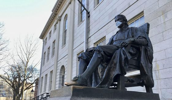 The John Harvard statue at Harvard University, a popular tourist attraction at the campus in Cambridge, Mass, sits adorned with a medical mask as students prepared to leave campus, Saturday, March 14, 2020. (AP Photo/Collin Binkley)  ** FILE **