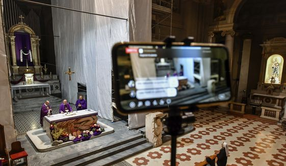 The Holy Mass is celebrated in an empty church and broadcasted in streaming online for the faithful in the San Luigi Gonzaga Parrish church in Milan, Italy, Sunday, March 15, 2020.  For most people, the new coronavirus causes only mild or moderate symptoms. For some, it can cause more severe illness, especially in older adults and people with existing health problems.  (Claudio Furlan/LaPresse via AP)  **FILE**