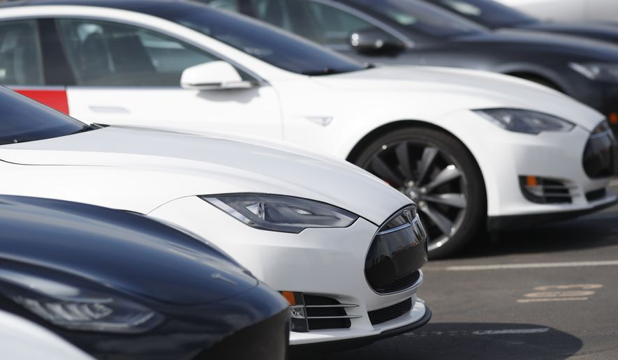 In this Sunday, March 15, 2020, photograph, a long row of unsold 2020 Model S sedans sit at a Tesla dealership in Littleton, Colo. (AP Photo/David Zalubowski)