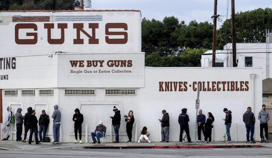 People wait in a line to enter a gun store in Culver City, Calif., Sunday, March 15, 2020. Coronavirus concerns have led to consumer panic buying of grocery staples and now gun stores are seeing a similar run on weapons and ammunition as panic intensifies. (AP Photo/Ringo H.W. Chiu)