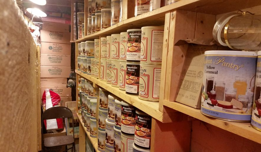 """In this undated photo provided by Paul Buescher, canned food rests on shelves in a barn near Garretsville, Ohio. The food can be used by 32 members of a group in northeastern Ohio that shares a farm packed with enough canned and dehydrated food and water to last for years. For those in the often-mocked """"prepper"""" community, this is quickly becoming their """"I told you so"""" moment, as panic buying has cleared store shelves across the U.S. amid growing fears that the new coronavirus will force many Americans to self-quarantine for weeks in their homes. (Paul Buescher via AP)"""