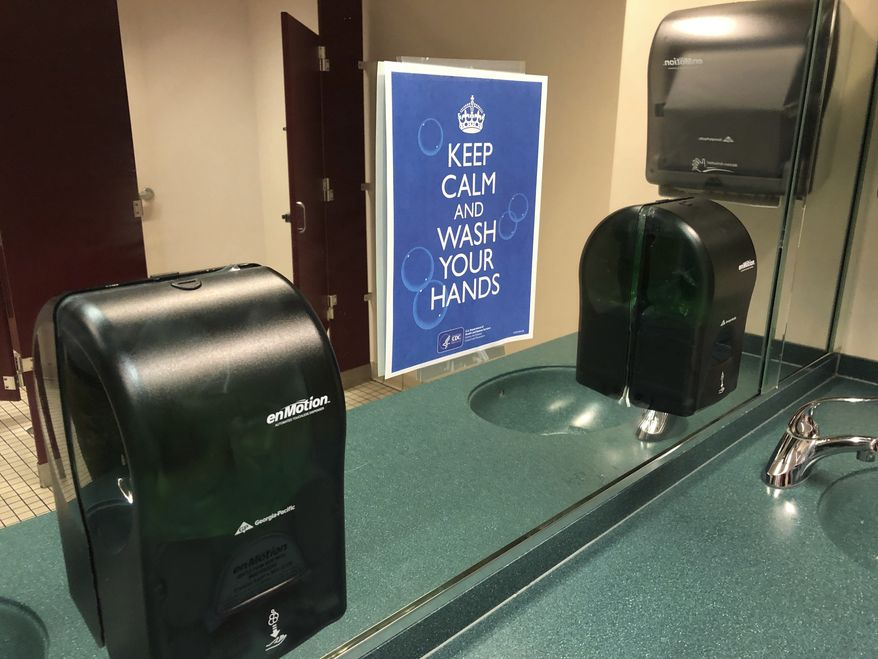 A sign advises hand-washing in a bathroom at St. Philip African Methodist Episcopal Church in Atlanta on Sunday, March 15, 2020. Only about 100 people filled a sprawling sanctuary that seats more than a thousand at the church because of coronavirus fears. Pastor William Watley told congregants he would follow officials' guidance on whether to continue services after Sunday, calling for prayer during the epidemic. (Jeff Amy/Associated Press)