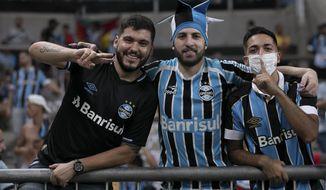 Fans of Brazil's Gremio pose for a photo prior to a Copa Libertadores soccer match against Internacional at Gremio Arena in Porto Alegre, Brazil, Thursday, March 12, 2020. (AP Photo/Liamara Polli)