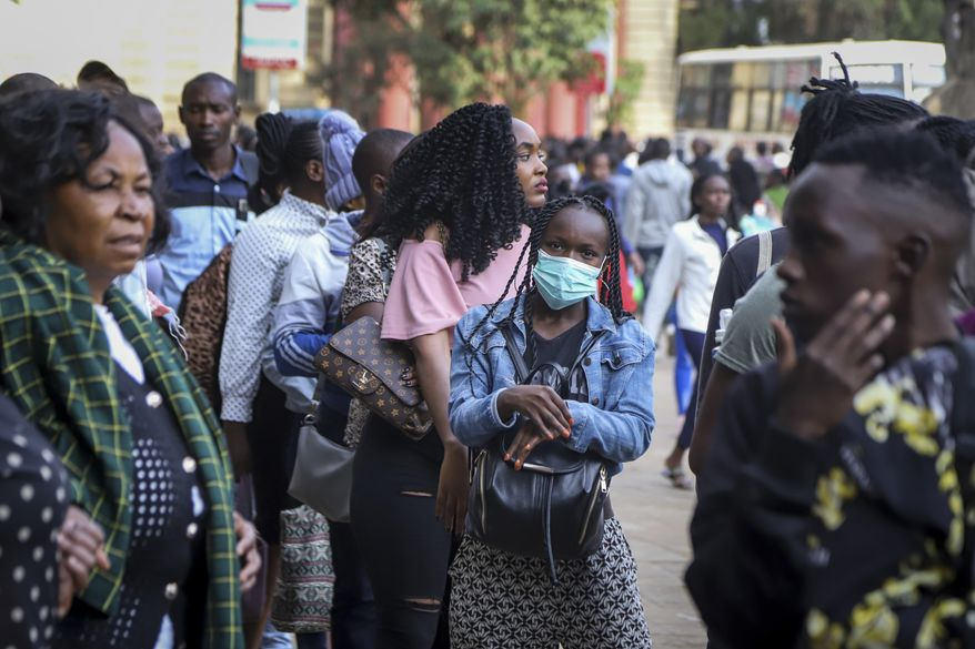 A Kenyan woman wears a surgical face mask on a busy street in downtown Nairobi, Kenya Friday, March 13, 2020. Authorities in Kenya said Friday that a Kenyan woman who recently traveled from the United States via London has tested positive for the new coronavirus, the first case in the East African country. (AP Photo/Patrick Ngugi)