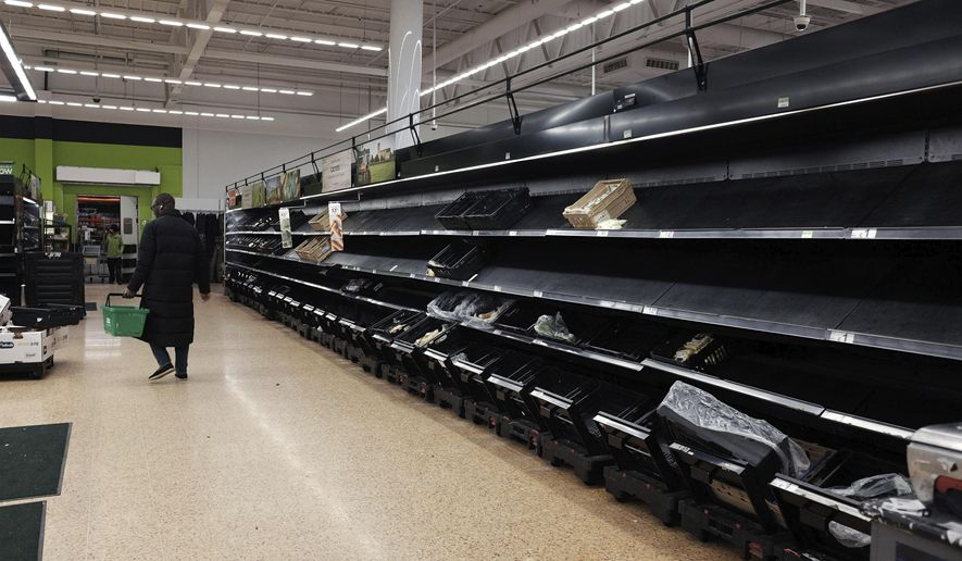 Shelves are empty in the fruit and vegetable section of an Asda store in London on Saturday, March 14, 2020. (Yui Mok/PA via AP)
