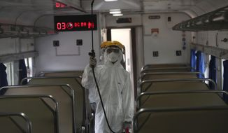 An employee in protective gears sprays disinfectant in the wake of coronavirus outbreak inside a train at the Senen train station in Jakarta Indonesia, Sunday, March 15, 2020. Indonesia's capital city announced a lockdown of all tourist destinations and entertainment spots as well as the closing all of its public schools for the next 14 days amid the global outbreak. For most people, the new coronavirus causes only mild or moderate symptoms. For some it can cause more severe illness. (AP Photo/Tatan Syuflana)