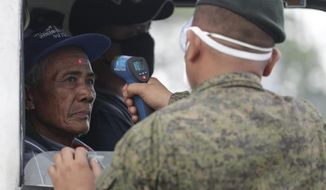 A man's temperature is checked by an army trooper before entering the metropolis at a checkpoint on the outskirts of Quezon city, Philippines Sunday, March 15, 2020. Thousands of Philippine police, backed by the army and coast guard, have started sealing the densely populated capital from most domestic travelers in one of Southeast Asia's most drastic containment moves against the coronavirus. For most people, the new coronavirus causes only mild or moderate symptoms. For some, it can cause more severe illness, especially in older adults and people with existing health problems. (AP Photo/Aaron Favila)