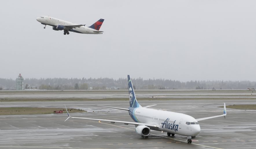 In this April 13, 2018, photo, a Delta Air Lines plane takes off above a taxiing Alaska Airlines airplane at the Seattle-Tacoma International Airport in Seattle.  U.S. airlines are asking the federal government for grants, loans and tax relief that could easily top $50 billion to help them recover from a sharp downturn in travel due to the new coronavirus. Airlines for America, the trade group representing the carriers, posted its request for financial help on Monday, March 16, 2020, just as more airlines around the world were announcing ever-deeper cuts in service and, in some cases, layoffs. (AP Photo/Ted S. Warren) **FILE**