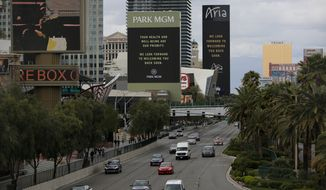 The Park MGM and Aria hotel-casinos flash messages on their closing due to the coronavirus, Monday, March 16, 2020, in Las Vegas. MGM Resorts International and Wynn Resorts will close their Las Vegas properties as of March 17 in light of the coronavirus pandemic. (AP Photo/John Locher)
