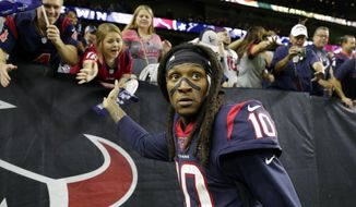 FILE - In this Jan. 4, 2020, file photo, Houston Texans wide receiver DeAndre Hopkins celebrates with fans after an NFL wild-card playoff football game against the Buffalo Bills in Houston. The Arizona Cardinals have acquired three-time All-Pro receiver DeAndre Hopkins in a trade that will send running back David Johnson and draft picks to the Houston Texans, a person familiar with the situation told The Associated Press. The person spoke to the AP on condition of anonymity Monday, March 16, 2020, because the trade hasn't been officially announced. (AP Photo/Michael Wyke)