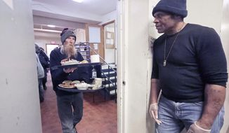 Doug Porteous, 57, carries two trays of food with Manuel Watkins, 54, standing by door of the men's homeless shelter at Grace Episcopal Church in Madison, Wis. Wednesday, Feb. 19, 2020. Both are homeless but also volunteer at the shelter. Watkins' wife was spending the night at the shelter for women and families on the other side of the city's Capitol Square.(John Hart/Wisconsin State Journal via AP)