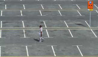 A parking lot attendant walks through a typically full parking lot now largely empty over people staying home due to the worldwide coronavirus pandemic in Dubai, United Arab Emirates, Monday, March 16, 2020. For most people, the new coronavirus causes only mild or moderate symptoms. For some it can cause more severe illness. (AP Photo/Jon Gambrell)