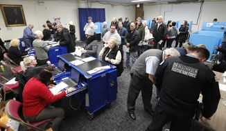 Chicago residents line up for early voting at the Roden Library Monday, March 16, 2020, in Chicago. (AP Photo/Charles Rex Arbogast)